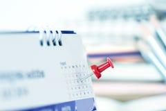 在日历页的红色图钉为提醒和被标记的重要前夕 免版税库存图片
