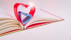 在日志书的红色和蓝色心脏在白色桌光在心脏的上面飘动 免版税库存照片