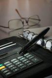 在日志和计算器的笔在背景玻璃 库存照片