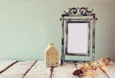 在日志树旁边的老维多利亚女王时代的钢青色空白框架与神仙的圣诞灯和房子灯笼在木桌上 免版税库存图片
