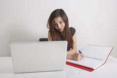 在日志的女实业家文字,当看膝上型计算机在办公室时 免版税库存图片