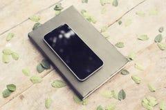 在日志的空白的黑智能手机屏幕与在木选项的叶子 库存图片