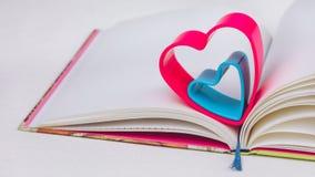 在日志的红色和蓝色心脏在白色桌上预定 免版税库存图片