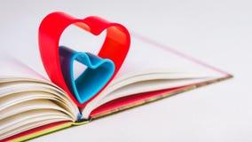 在日志的红色和蓝色心脏在白色桌上预定 库存照片