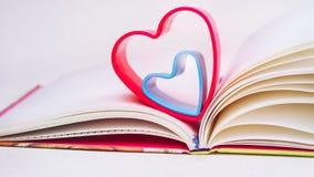 在日志的红色和蓝色心脏在白色桌上预定 图库摄影