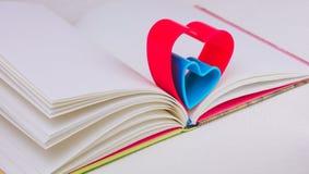 在日志的红色和蓝色心脏在白色桌上预定 库存图片