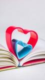 在日志的红色和蓝色心脏在白色桌,垂直的取向上预定 库存图片