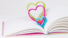 在日志的红色蓝色和绿色心脏在白色桌上预定 免版税库存照片