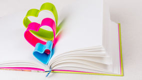 在日志的蓝色红色和绿色心脏在白色桌上预定 免版税库存照片