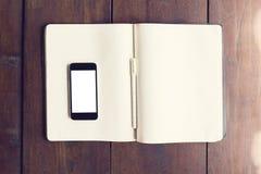 在日志空白页的空白的智能手机屏幕与笔的在woode 免版税库存照片