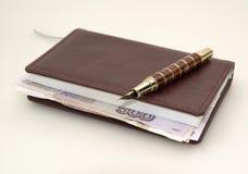 在日志里面的卢布金钱和笔 免版税库存照片