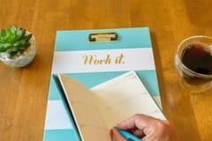 在日期记事录的妇女` s被修剪的手文字在有词`工作的剪贴板它` 库存照片