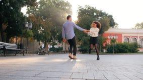 在日期,人拥抱和转动妇女的年轻企业夫妇 女孩跳进男朋友` s胳膊,旋转她的他在 股票视频