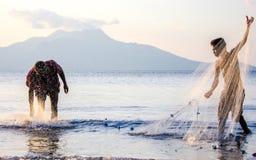 在日落、地方渔夫和年轻学徒,弗洛勒斯, Indo,亚洲的捕鱼网 免版税库存图片