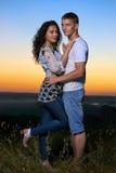 在日落、美好的风景和明亮的黄色天空,爱柔软概念,年轻成人人民的浪漫夫妇容忍 免版税库存照片