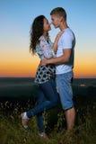 在日落、美好的风景和明亮的黄色天空,爱柔软概念,年轻成人人民的浪漫夫妇容忍 图库摄影