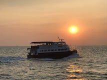 在日落下的一条小船 免版税库存照片