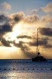 在日落下的一条游艇 免版税库存照片