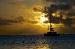 在日落下的一条游艇 库存图片