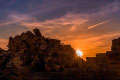 在日落下的古色古香的城市废墟与疏散云彩 库存照片
