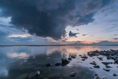 在日落与重的云彩, Ijselmeer叫声期间的反射的湖 免版税库存图片