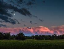 在日落乌云和绿草的桃红色云彩 库存图片