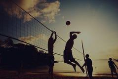 在日落享受概念的沙滩排球 免版税库存照片