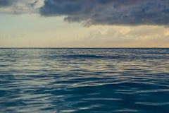 在日落以后的暮色天空在海滩 镇静低潮柔滑的海洋水 库存照片