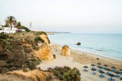 在日落以后的Barranco das卡尼亚斯海滩在波尔蒂芒,葡萄牙 坐,游泳在海和使用在海滩的人们 图库摄影