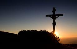在日落光的十字架 库存照片