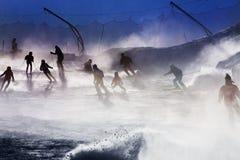 在日落光的许多滑雪者剪影 免版税库存图片