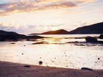 在日落内的步行在海滩 反映在海水的sunsetting的天际在岩石之间 免版税库存图片