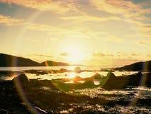 在日落内的步行在海滩 反映在海水的sunsetting的天际在岩石之间 图库摄影