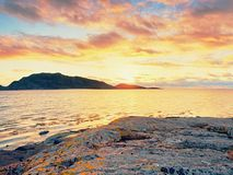 在日落内的步行在海滩 反映在海水的sunsetting的天际在岩石之间 免版税库存照片