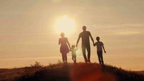 在日落剪影的愉快的家庭 库存照片