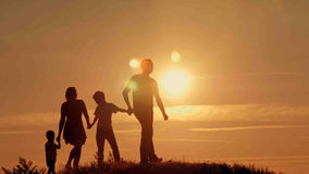 在日落剪影的愉快的家庭 免版税库存照片