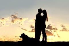 在日落剪影的爱恋的夫妇亲吻 免版税库存图片
