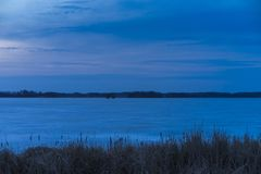 在日落和冰湖的好的新鲜的蓝色黄昏天空在瑞典 免版税库存图片