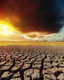 在日落和天旱地球的低黑暗的云彩 免版税库存图片