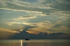 在日落和日出的小船与在海洋的剧烈的天空 免版税库存照片