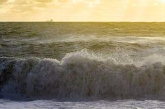 在日落和船的海波浪 免版税图库摄影