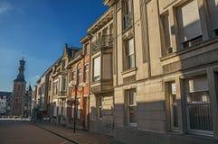 在日落和蓝色明亮的天空的塔、街道和房子门面在蒂尔特 库存照片