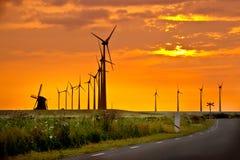 在日落天空前面的风车 免版税库存图片