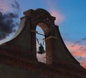 在日落天空的一座砖和灰泥钟楼 库存照片