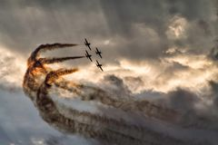 在日落天空的四架飞机形成在飞行表演 库存照片