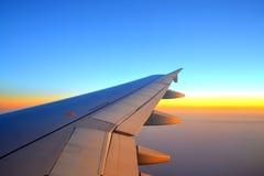 在日落天空的平面翼 库存图片