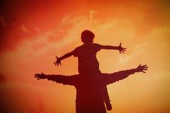 在日落天空的父亲和儿子戏剧 库存照片