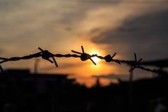 在日落天空的老铁丝网剪影 免版税图库摄影