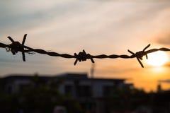 在日落天空的铁丝网剪影 图库摄影