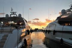 在日落天空背景的两条游艇 免版税库存照片